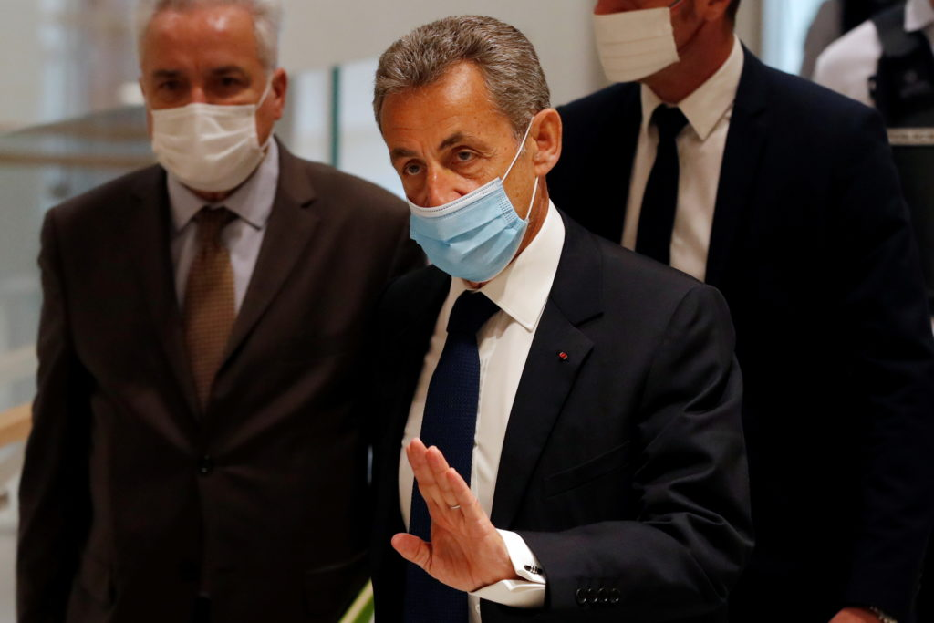 Former French President Nicolas Sarkozy, wearing a protective face mask, arrives for the verdict in his trial on charges o...