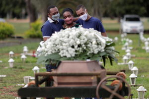 Gerson James, 34, and Jeferson James, 18, embrace their mother Izenilde Jesus, 55, during the funeral of their father Frank James Santana, 54, who died from the coronavirus disease (COVID-19), at the Campo da Esperanca cemetery, in Brasilia, Brazil, April 29, 2021. Photo by REUTERS/Ueslei Marcelino