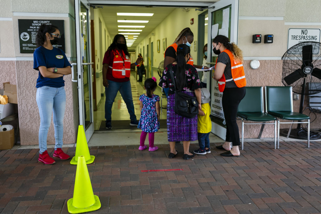 A woman confers with officials while waiting for her turn to get vaccinated at a COVID-19 vaccine event in southern Florid...