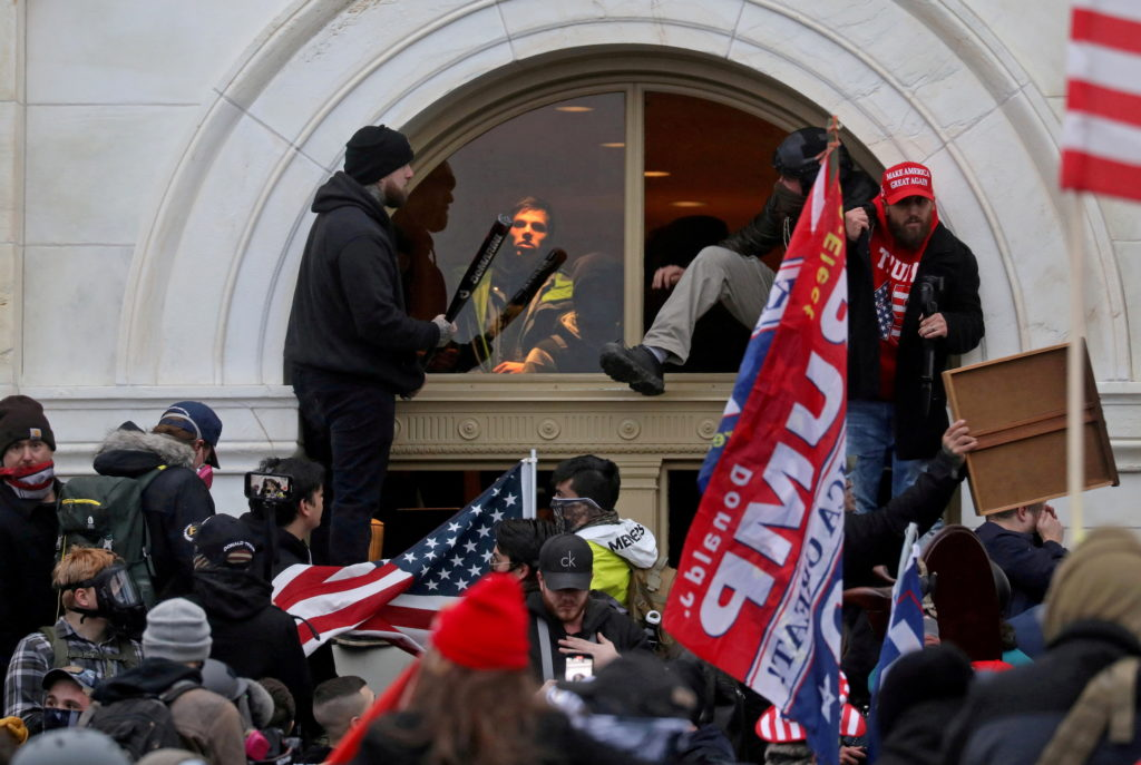 A mob of supporters of then-U.S. President Donald Trump climb through a window they broke as they storm the U.S. Capitol B...