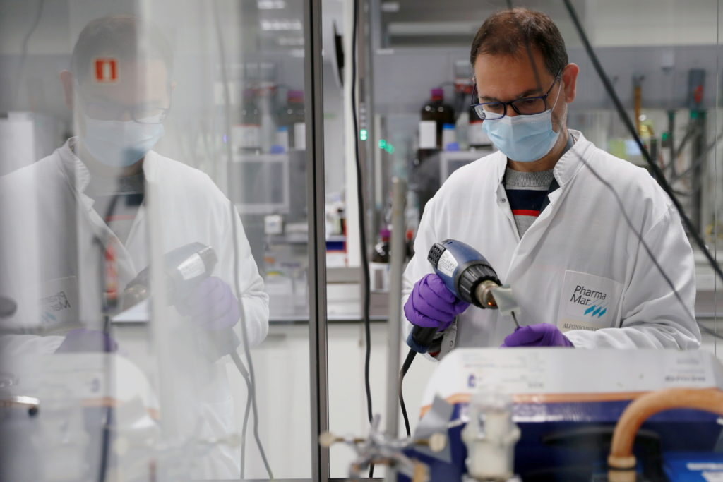 Lab worker wears a coat and mask