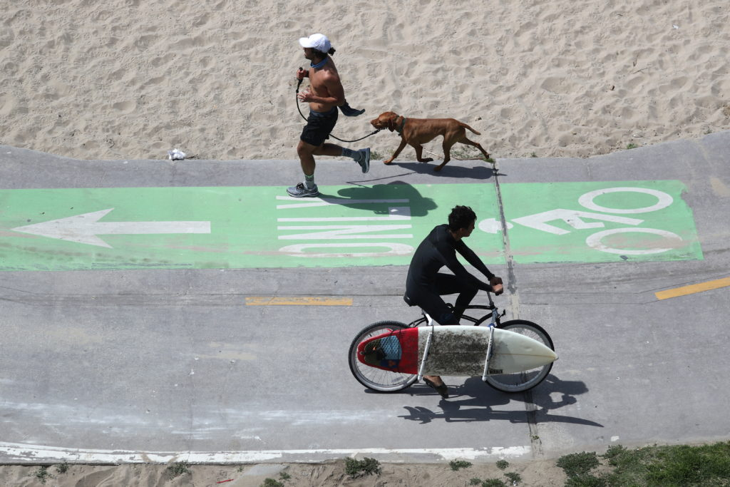 People exercise on the bike path, as the coronavirus disease (COVID-19) disease pandemic continues, on Venice Beach in Los...
