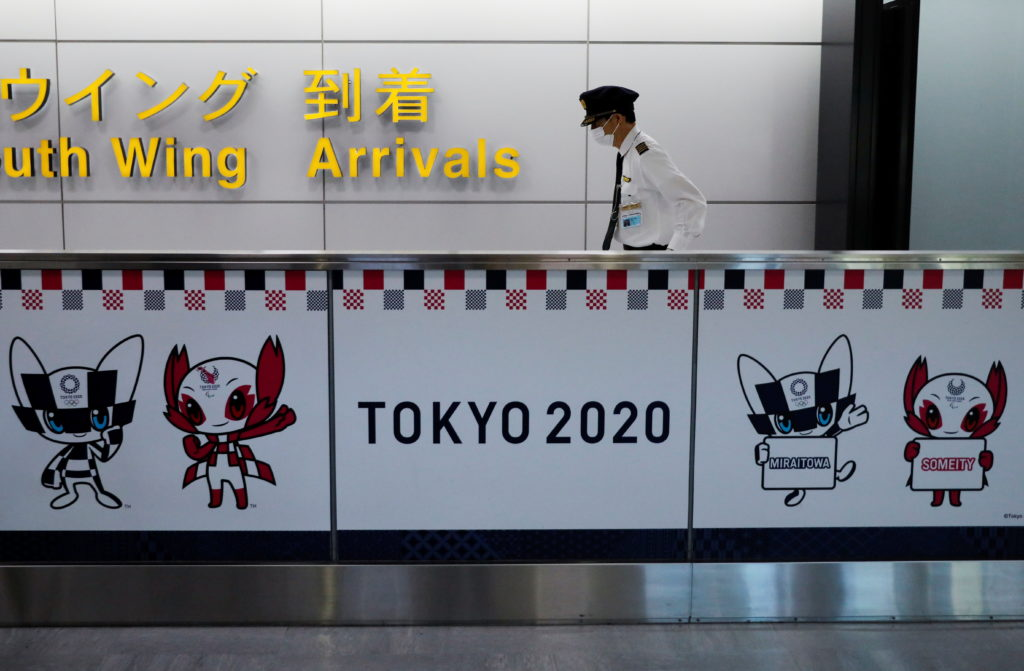 An employee of an airline company walks next to an advertisement for Tokyo 2020 Olympic and Paralympic Games at Narita int...
