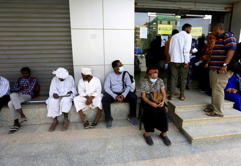 FILE PHOTO: People wait outside currency exchange bureau to receive money in Khartoum