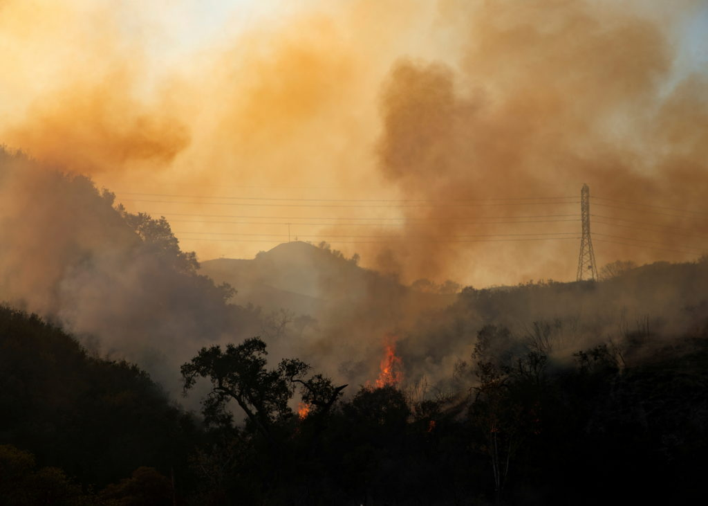 FILE PHOTO: The Bond Fire wildfire continues to burn next to electrical power lines near Modjeska Canyon, California