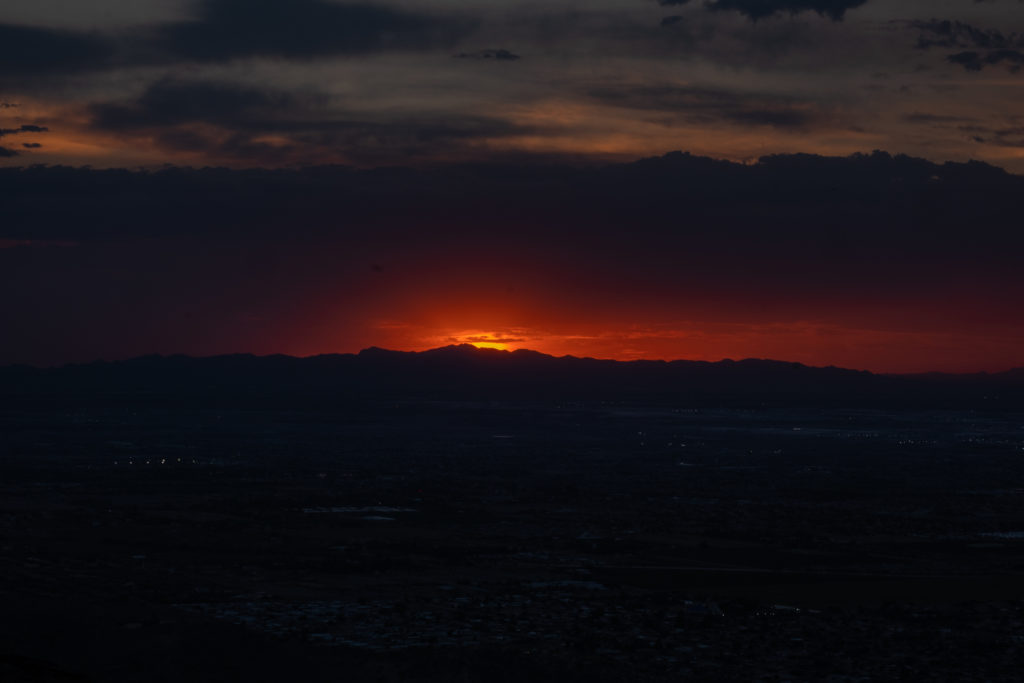 A hazy bright red sunset behind a mountain in Phoenix, Arizona.