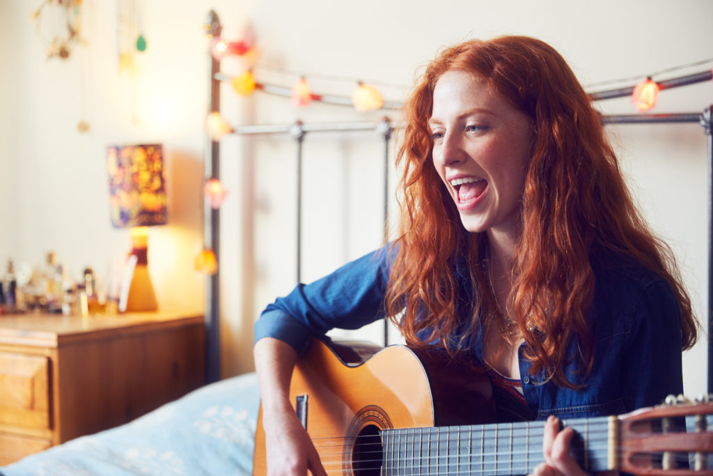 Young woman singing with guitar