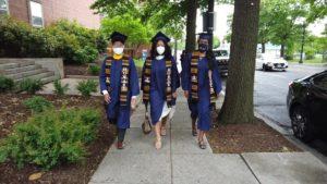 Three graduates of Howard University walk down a sidewalk