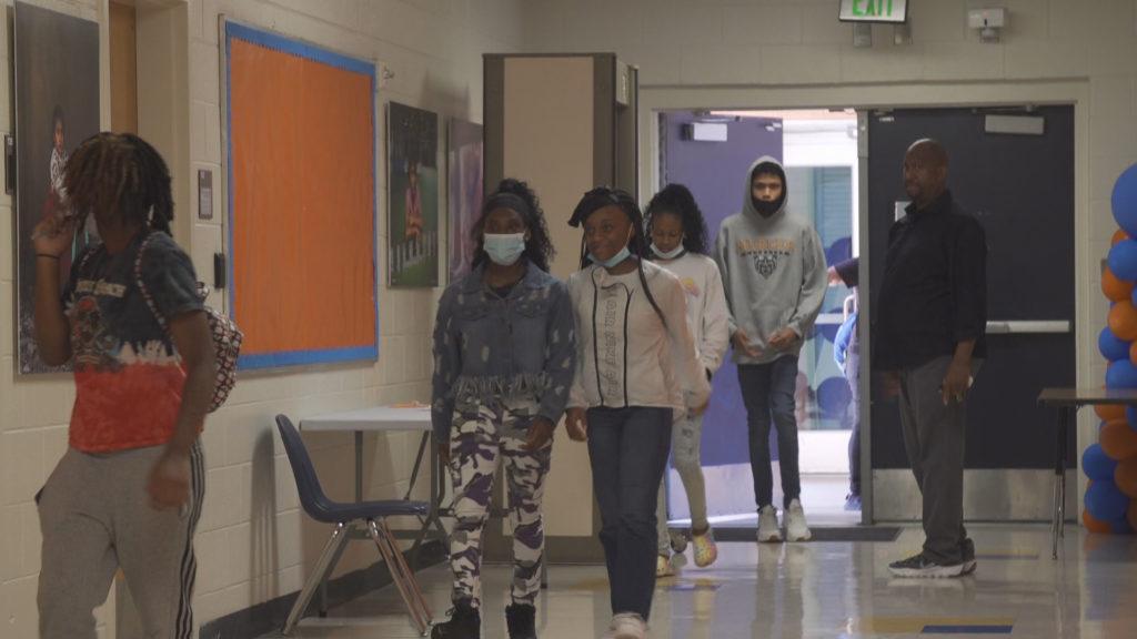 Middle schoolers in face masks walk in a school hallway