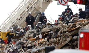 Emergency workers conduct search and rescue efforts at the site of a partially collapsed residential building in Surfside