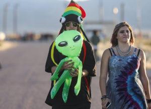 Two people walk outside Area 51 holding a balloon alien.