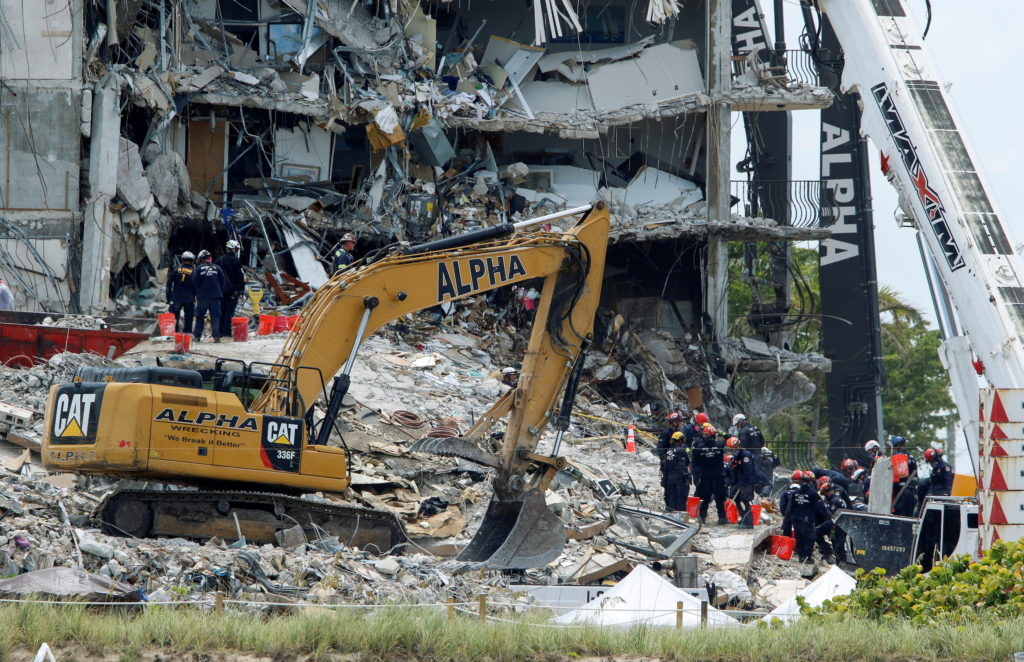 Emergency workers conduct search and rescue missions at the site of a partially collapsed residential building in Surfside