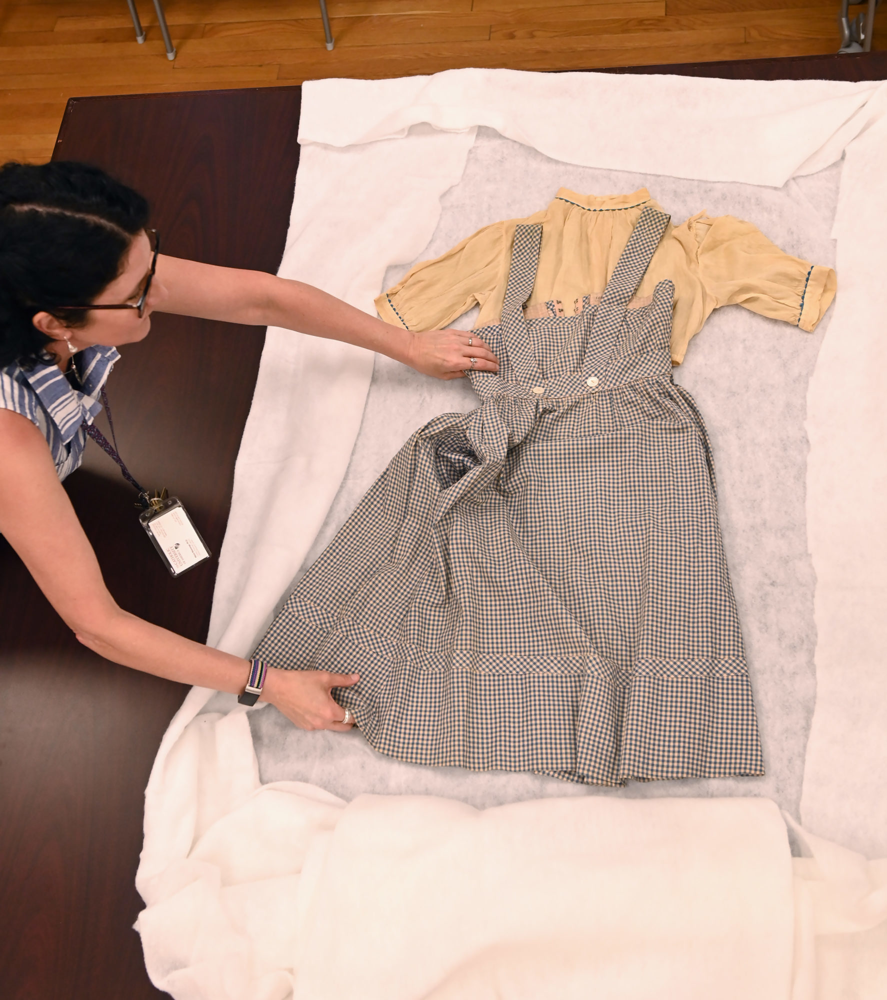 """Dr. Maria Mazzenga, curator, Special Collections at The Catholic University of America, displays the dress worn by actress Judy Garland's character Dorothy in the classic 1939 film """"The Wizard Of Oz."""""""