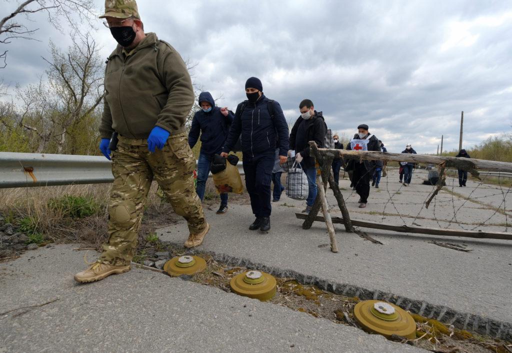Prisoners of war (POWs) (not in uniform), wearing protective masks amid the coronavirus disease (COVID-19) outbreak, walk ...