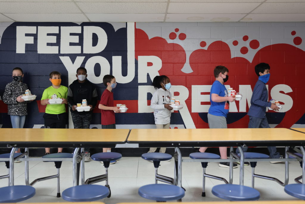 Older students carry their lunches to their classrooms to eat, leaving the lunchroom free for younger students to keep a s...