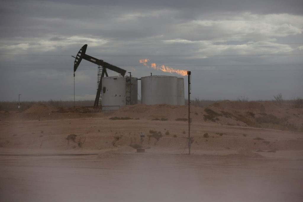 FILE PHOTO: Dust blows around a crude oil pump jack and flare burning excess gas at a drill pad in the Permian Basin in Lo...