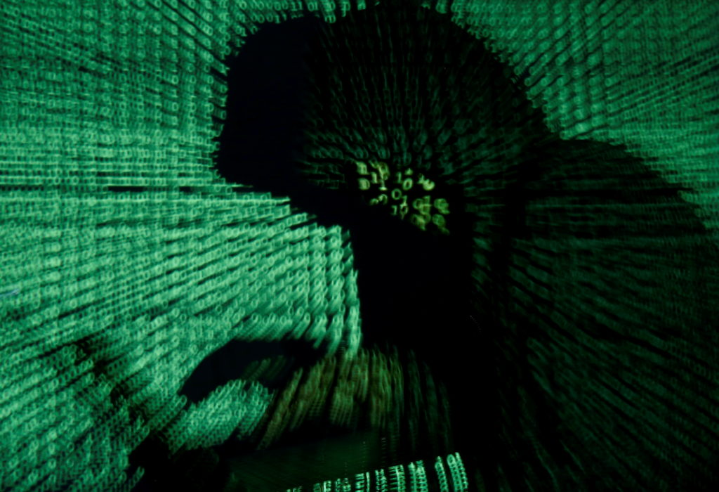 A man holds a laptop computer as cyber code is projected on him in this illustration picture taken on May 13, 2017. Photo ...