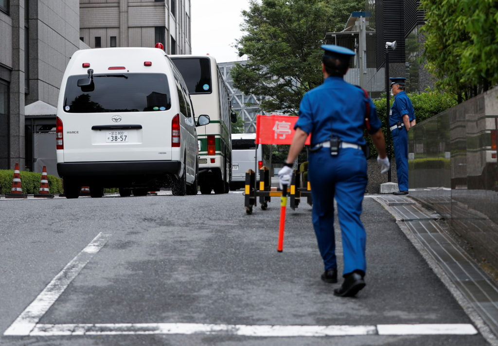 Buses believed to be carrying Michael Taylor and his son Peter arrive at the Tokyo district court