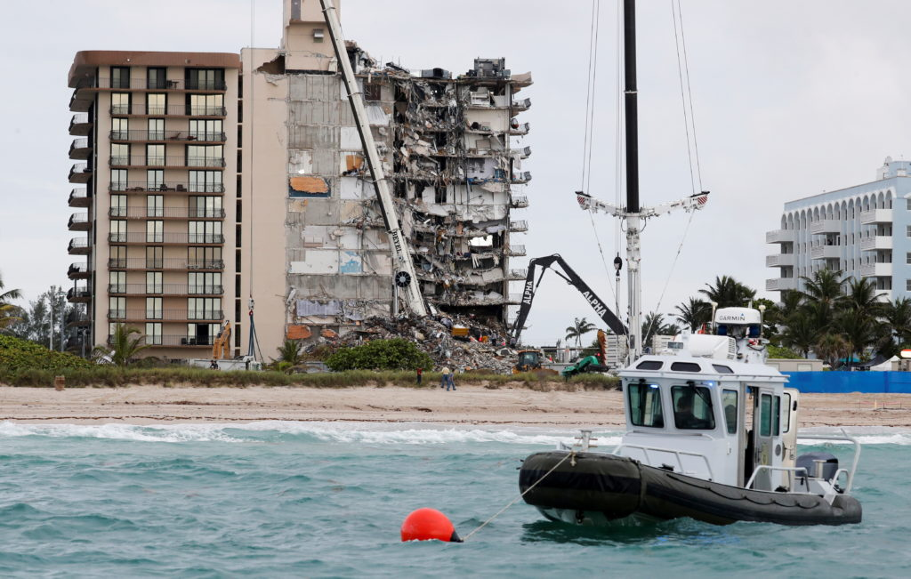 A Miami-Dade County police boat sits at anchor as emergency workers conduct search and rescue efforts at the site of a par...