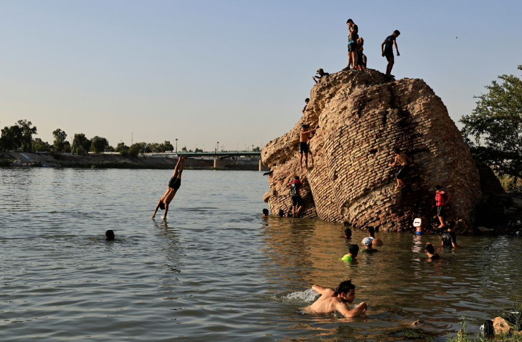 People dive into the Tigris river to cool down in the summer heat, in Baghdad