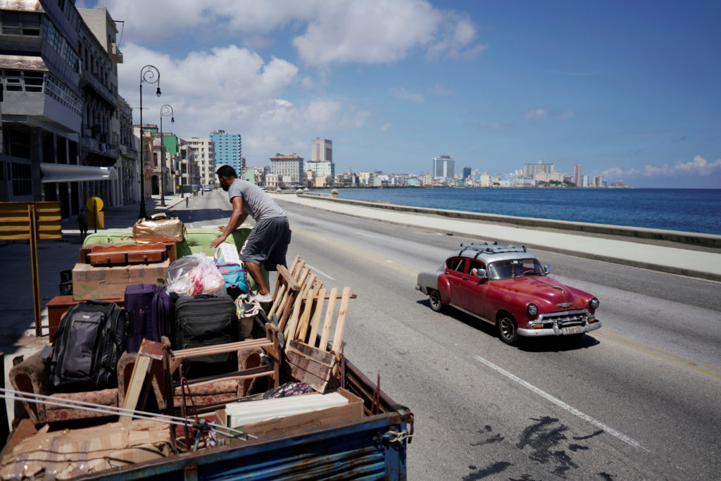 A man loads a truck with furniture from his home prior to the arrival of Storm Elsa, in Havana