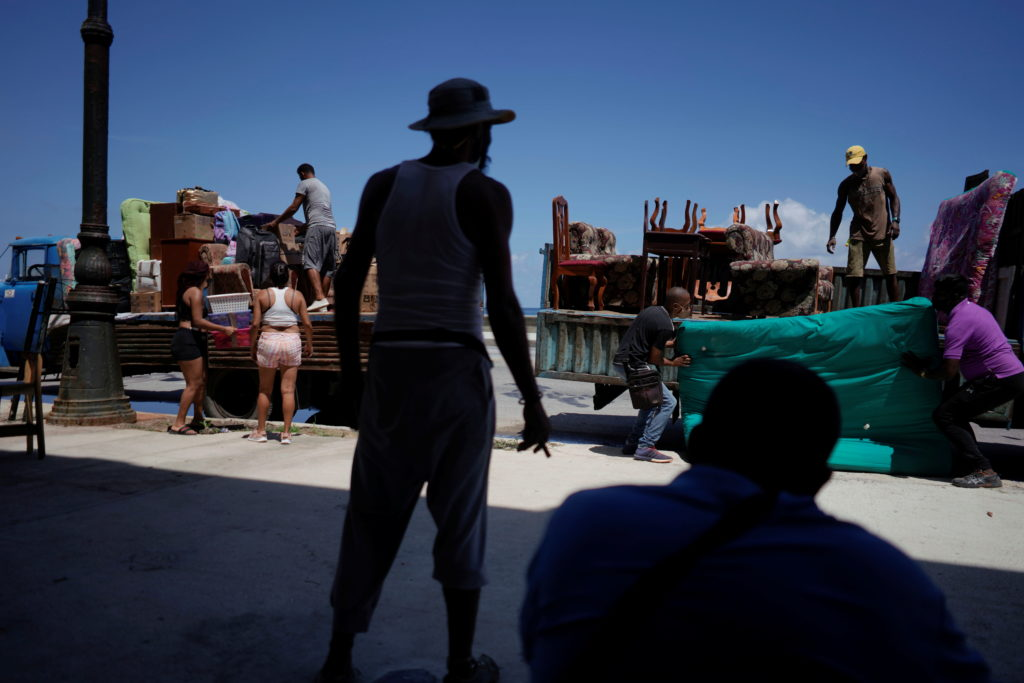 People load trucks with furniture to be relocated prior to the arrival of Storm Elsa, in Havana