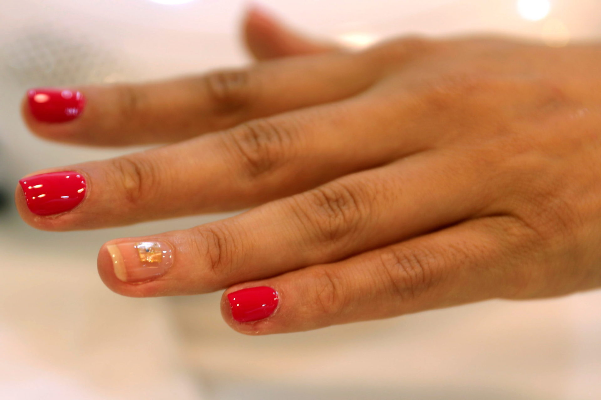 A customer gets a microchip, containing personal data, attached to one of her nails at Lanour Beauty Lounge in Dubai
