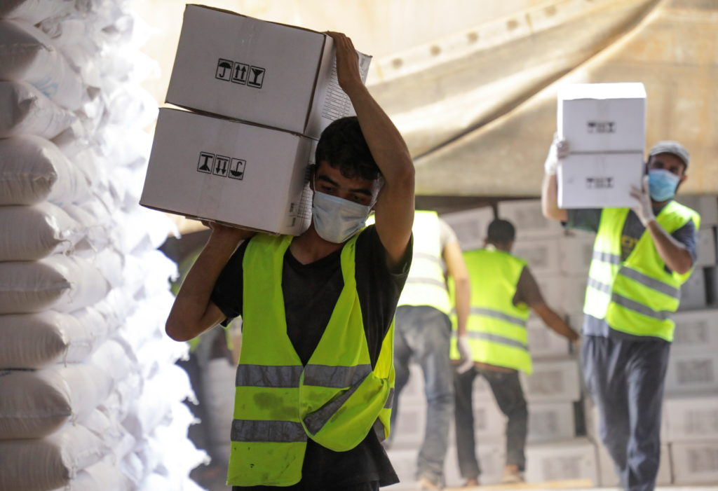 Workers carry boxes of humanitarian aid near Bab al-Hawa crossing at the Syrian-Turkish border, in Idlib governorate