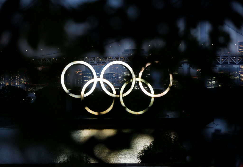 The giant Olympic rings are seen through a tree in the dusk in Tokyo