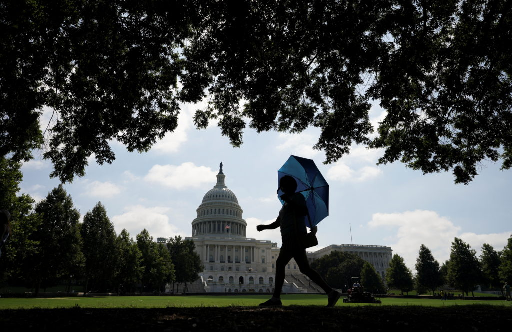 A woman holds an umbrella against the sun as she walks the grounds of the U.S. Capitol in Washington