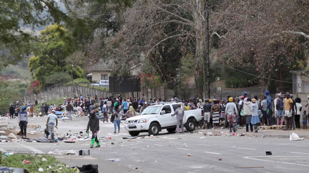 People stand on the roadside after being evicted following protests that have widened into looting, in Durban