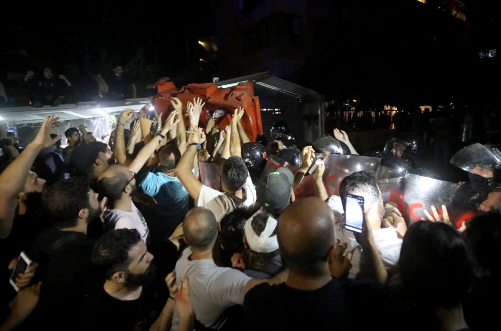 Demonstrators throw a barricade as they protest outside the home of the caretaker interior minister Mohamed Fahmy in Beirut