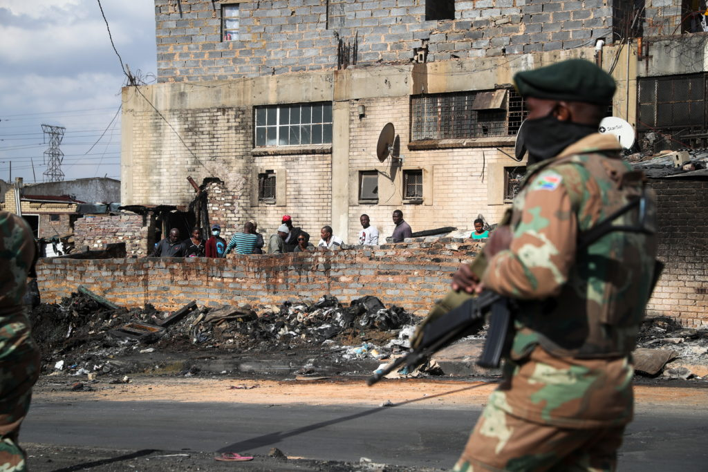Members of the military patrol through the streets of Alexandra township as the country deploys the army to quell unrest l...