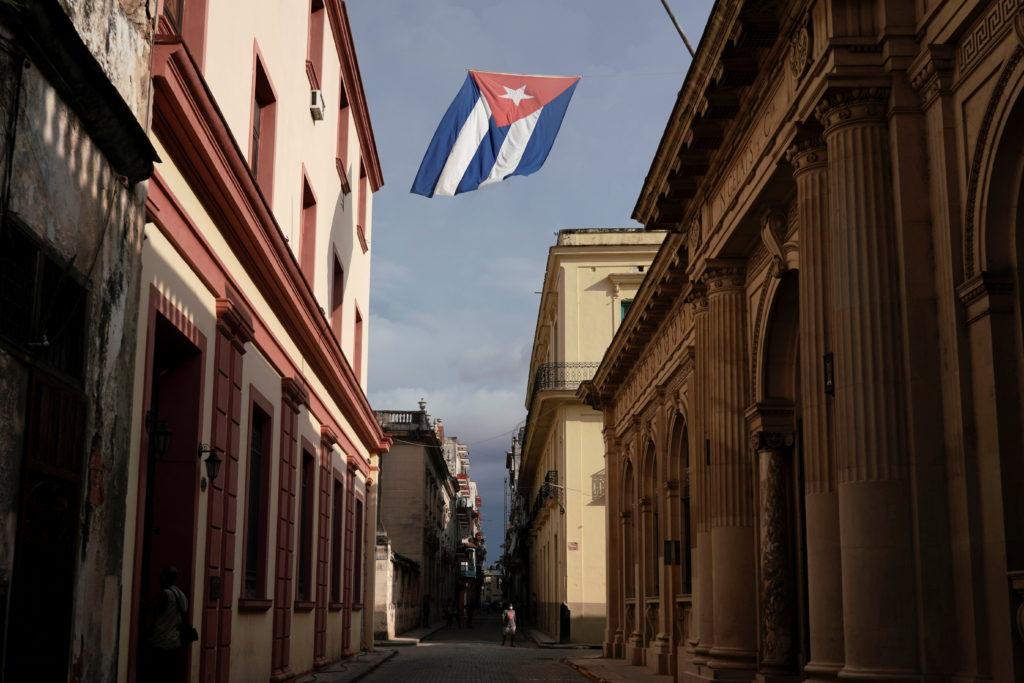 A Cuban flag flies over a street in downtown Havana