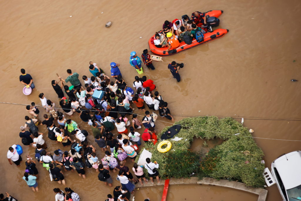 People standing on a flooded road wait to be evacuated following heavy rainfall in Zhengzhou