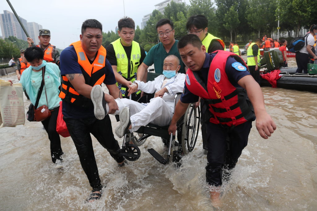 Rescue workers transfer a patient in a wheelchair at the Fuwai Central China Cardiovascular Hospital which was flooded fol...