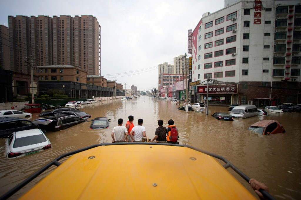 People ride a front loader as they wade through a flooded road following heavy rainfall in Zhengzhou