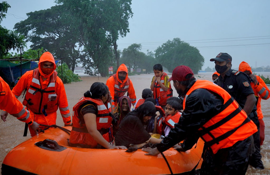Rescue workers evacuate people from a flooded area to safer places after heavy rains in Kolhapur