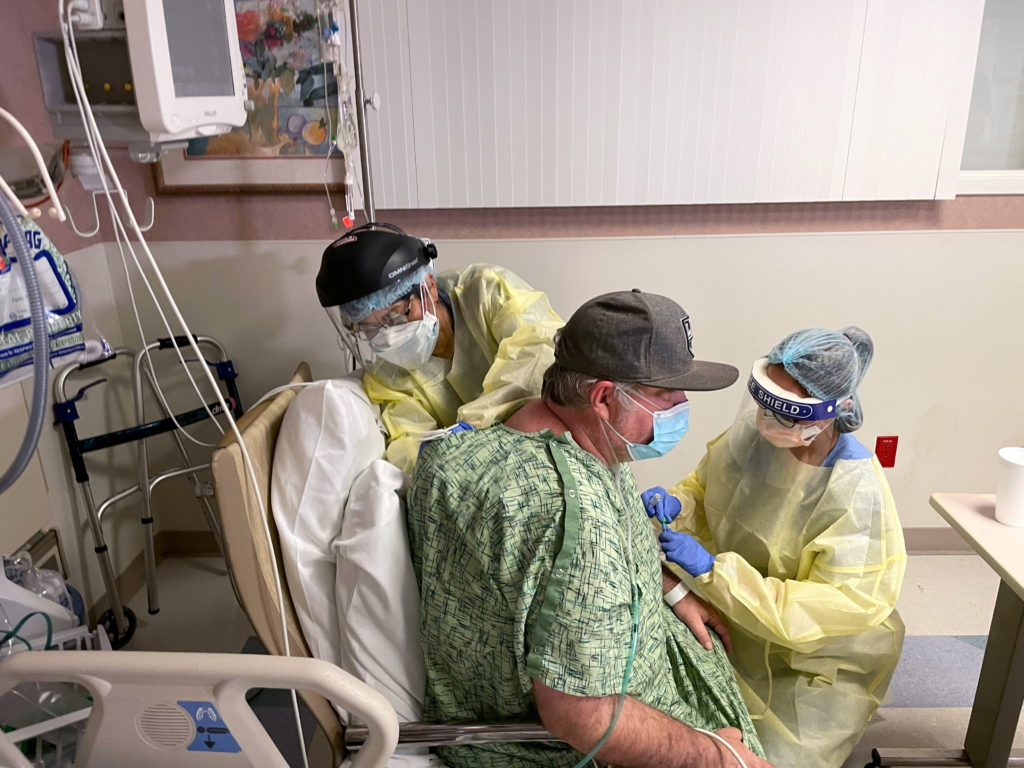 COVID-19 patient Brian Parisi is treated by staff in the ICU at Providence St Joseph Hospital in Orange, California