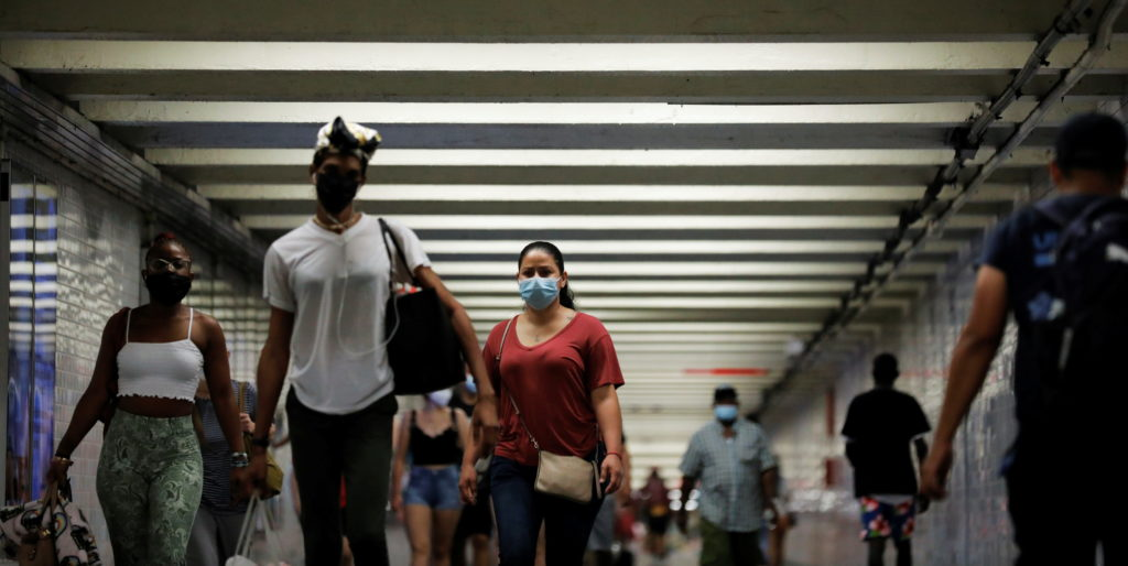 People wear masks as they pass through a pedestrian subway as cases of the infectious coronavirus Delta variant continue t...