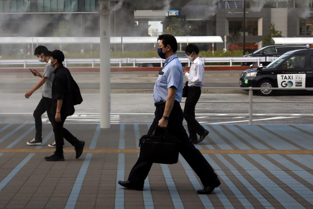 Commuters wearing protective masks make their through a cooling water mist in Tokyo