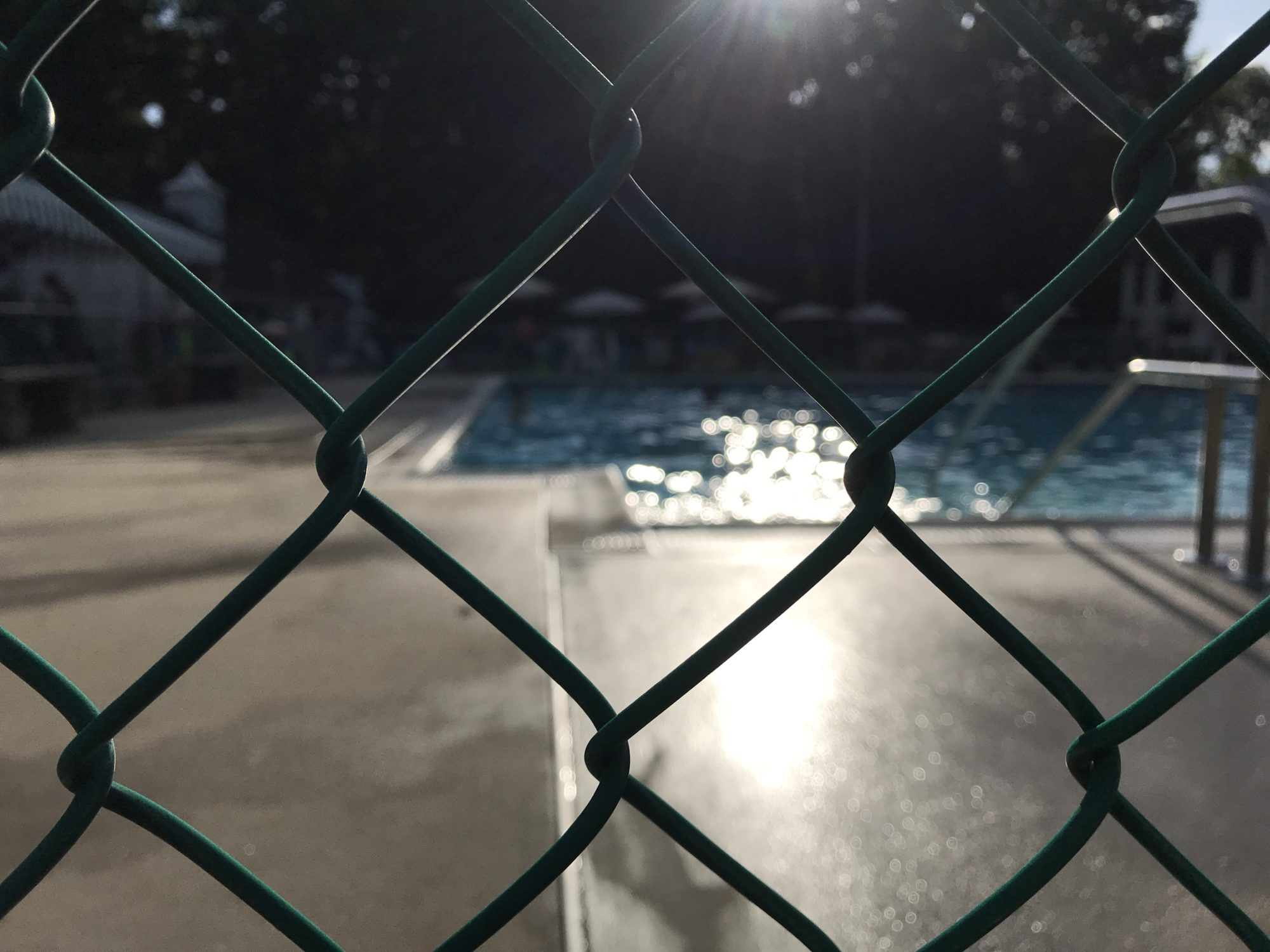 View Through a Fence of Late Afternoon Sunlight at the Pool