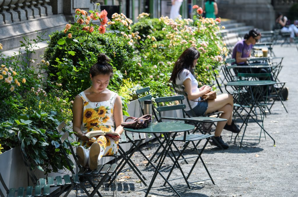US-WEATHER People sit in the sun on a warm day at Bryant Park on June 7, 2021 in New York City. (Photo by Angela Weiss / A...