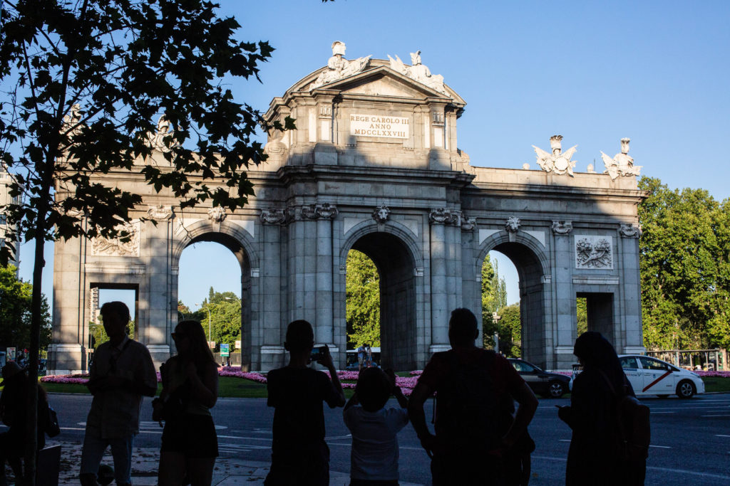 People take pictures of the Puerta de Alcalá in the center
