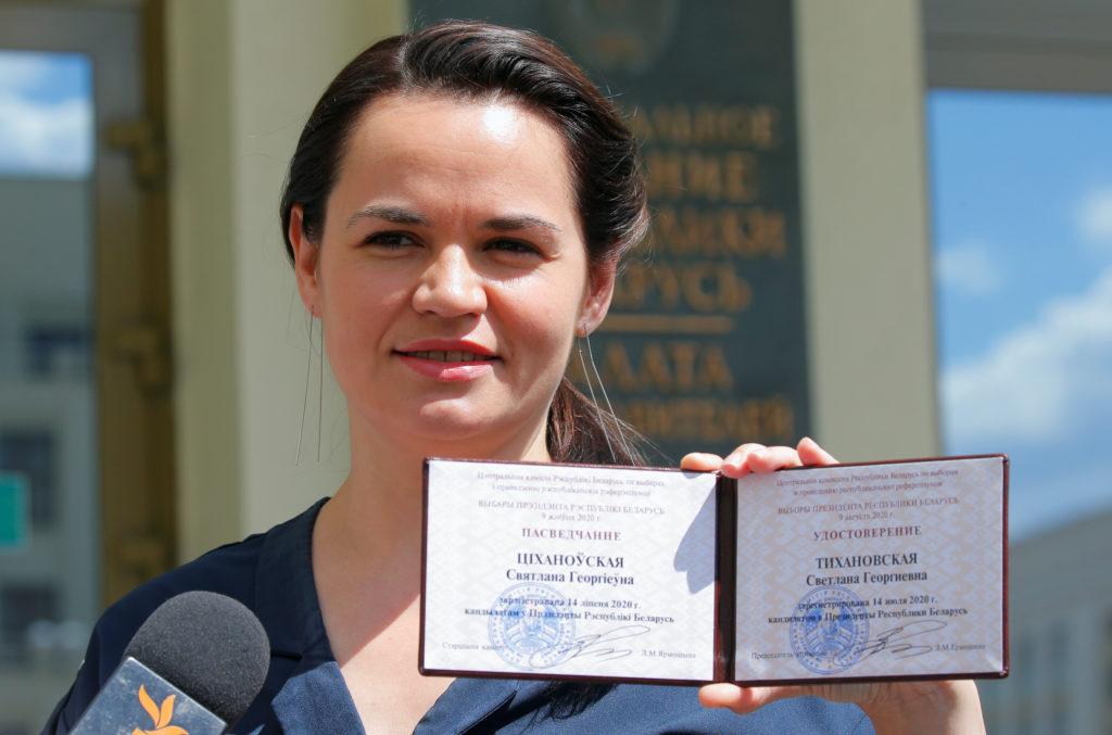 Presidential candidate Svetlana Tikhanovskaya shows her registration certificate as she leaves the central election commis...