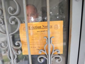 Milwaukee County Sheriff's Deputy Kevin Callahan places an eviction notice in the doorway of an apartment during an evicti...