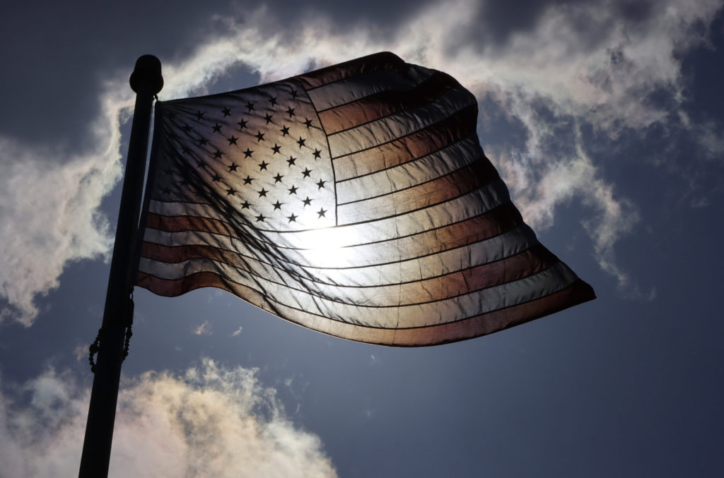 The sun shines through an American Flag at Mt. Mitchell Scenic Overlook in Atlantic Highlands, New Jersey