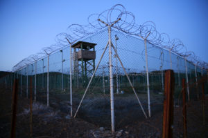Chain link fence and concertina wire surrounds a deserted guard tower within Joint Task Force Guantanamo's Camp Delta