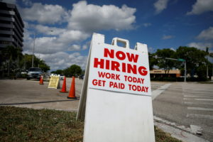"""FILE PHOTO: A """"Now Hiring"""" sign advertising jobs at a hand car wash is seen in Miami"""