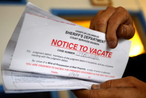 FILE PHOTO: Vicente Oliveros holds up his eviction notice in Los Angeles
